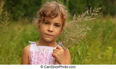girl is holding the blades of grass which she has gathered...