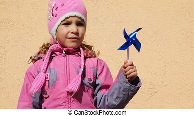 girl holding toy windmill left hand while standing near...