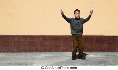 boy jumping on skipping rope in yard against house wall