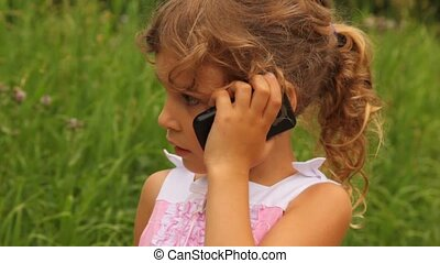 girl is speaking on her mobile phone in the park sunny...