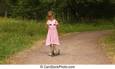 girl is riding scooter merrily along the park road - girl is...