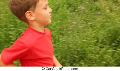 boy is running merrily across a field warm sunny day.
