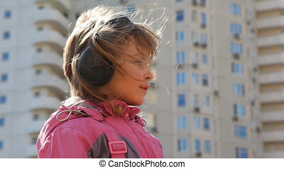 girl standing in yard with headphones and listening music,...