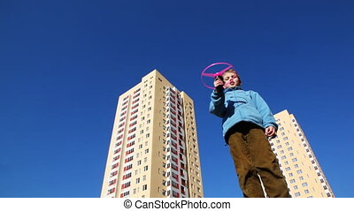boy runs toy helicopter against backdrop of high-rise...