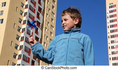 boy holding toy windmill against backdrop of high-rise...