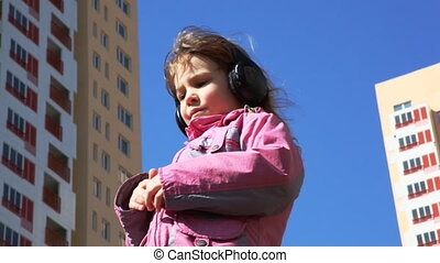 girl standing in yard with headphones