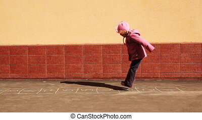 girl playing hopscotch jumps with both feet in yard