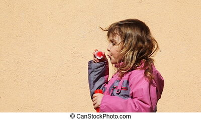 girl inflate housing bubbles in yard standing sideways to...