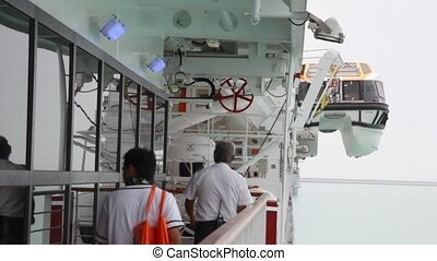staff of a cruiseship is going on the deck during safety...
