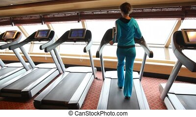 back view on woman running in gym - back view on slim woman...
