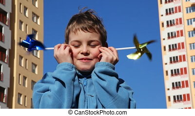 boy put his cheek two toys windmill against backdrop of...