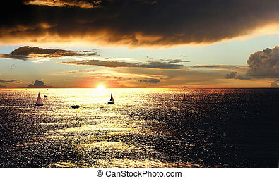 Sunset over the sea with boats