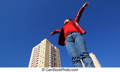 woman turns raising hands upward and outward palms up -...