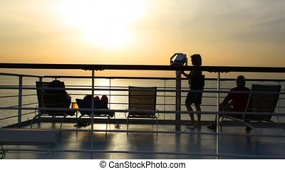silhouettes of people on deck of cruise ship against sunset...
