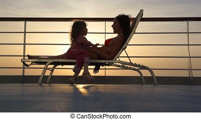 silhouettes of mother and daughter on deckchair of ship...
