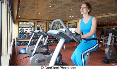 woman training on exercise bicycle - smiling woman training...