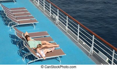 woman and girl lying on deck chairs - side view of woman and...