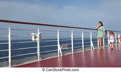 woman and daughter have joined hands and walks on deck -...
