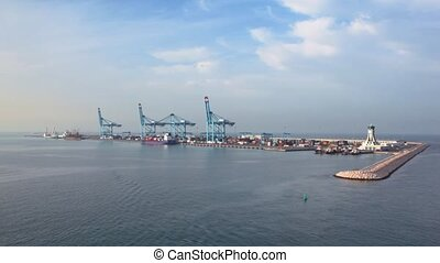 camera moving past by sea freight dock with cranes