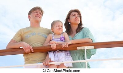 family rests at sea and looks far from the deck - young...