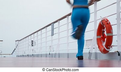 woman runs on deck of cruise ship - young woman runs on deck...
