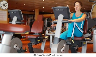 woman reverse spinning on exercise bicycle in gym
