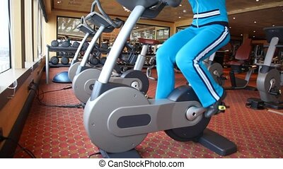 legs of woman working out on spinning bicycle in gym