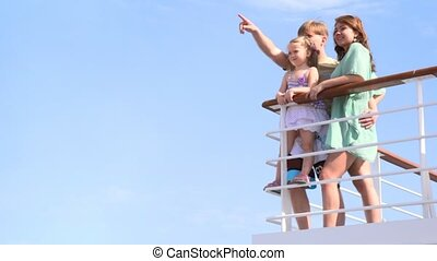 family is standing at railing on deck
