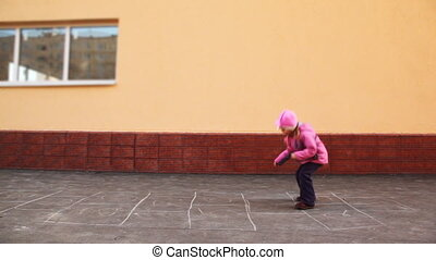 boy and girl playing hopscotch jumping - boy and girl...