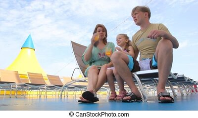 family drink juice, sitting on deckchairs