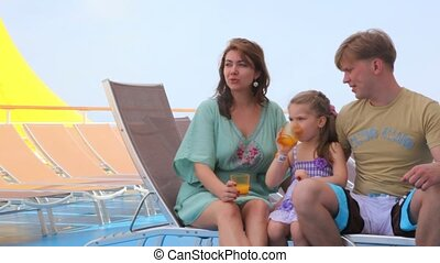 family rest on deck of cruise ship - family of three people...