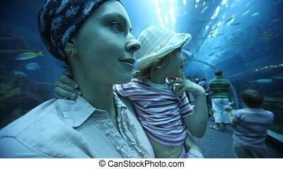 woman holding daughter in oceanarium