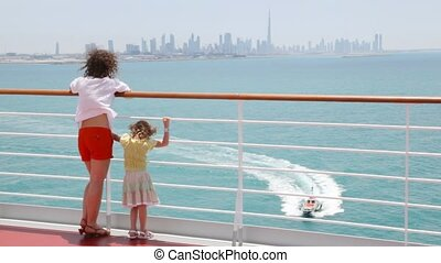 woman and girl are standing on deck looking at catamaran