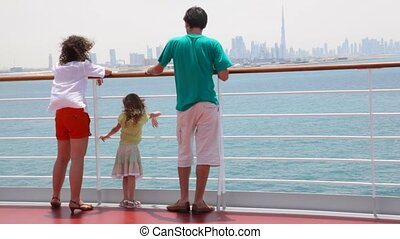 family is standing on deck of cruise ship - family of three...