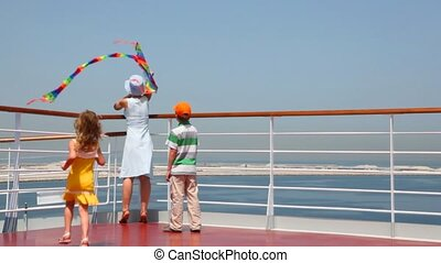 back view on family flying a kite on deck of ship