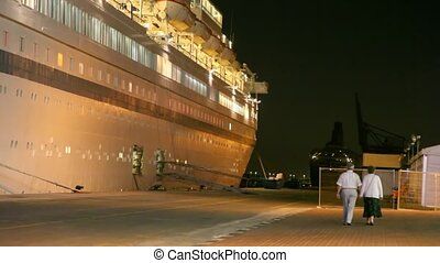 elderly couple is walking away from camera along a cruise...