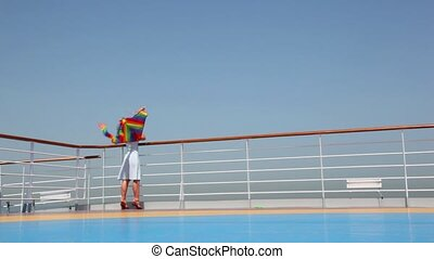 general view on woman flying kite on deck