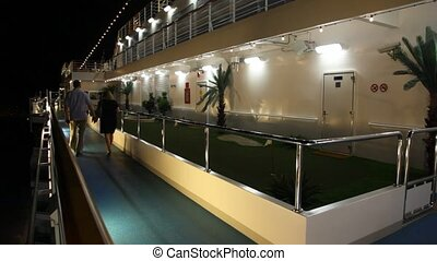 couple is walking on deck of cruise ship in the evening
