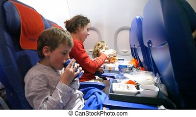 family is eating and drinking in the airplane