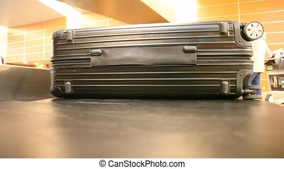 very close shot on suitcase lying on moving luggage belt