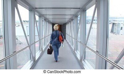 woman is going away on boarding bridge - One woman is going...