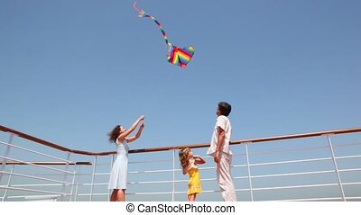 bottom view on family flying kite on deck of ship