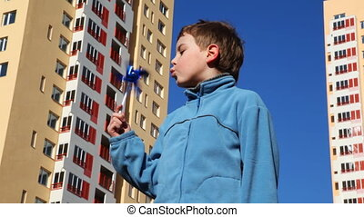 boy holding in his hand and blows on toy windmill against...