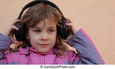 girl puts on headphones, listens to music and dancing