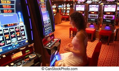 Woman at slot machine in play room in Persian Gulf - PERSIAN...