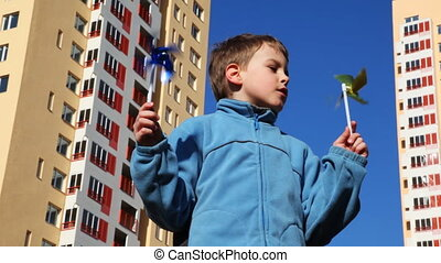 boy holds in his hands and blows on two toys windmill...
