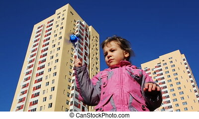 girl holding toy windmill against backdrop of high-rise...