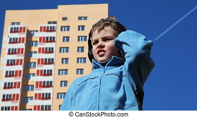 boy stands in courtyard with headphones against backdrop of...