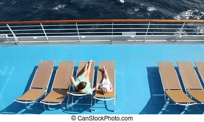 woman and girl are lying on the deck chairs