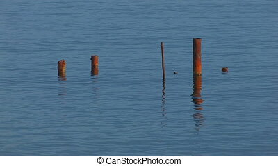 rusty metal pipes in the water